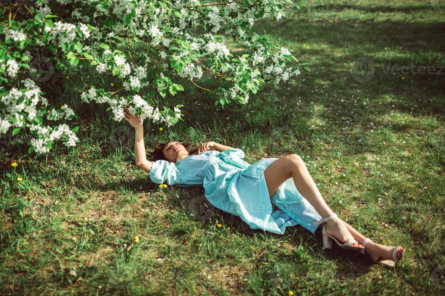 Girl lies in the park on the grass under a blooming apple tree photo