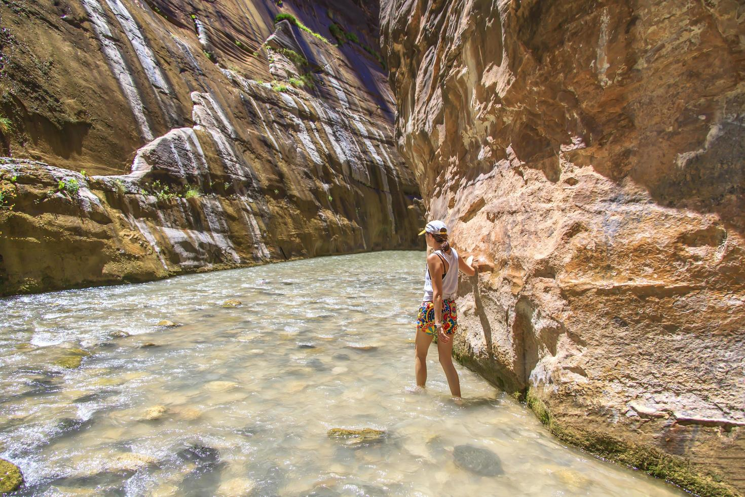 Woman walking through a river in the bottom of a canyon photo