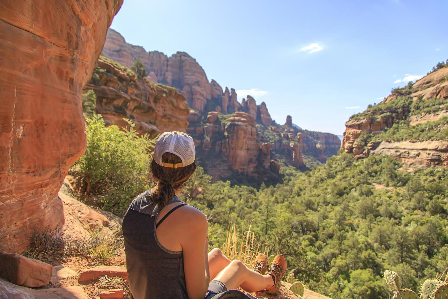 Woman looking down into a green canyon in the desert photo