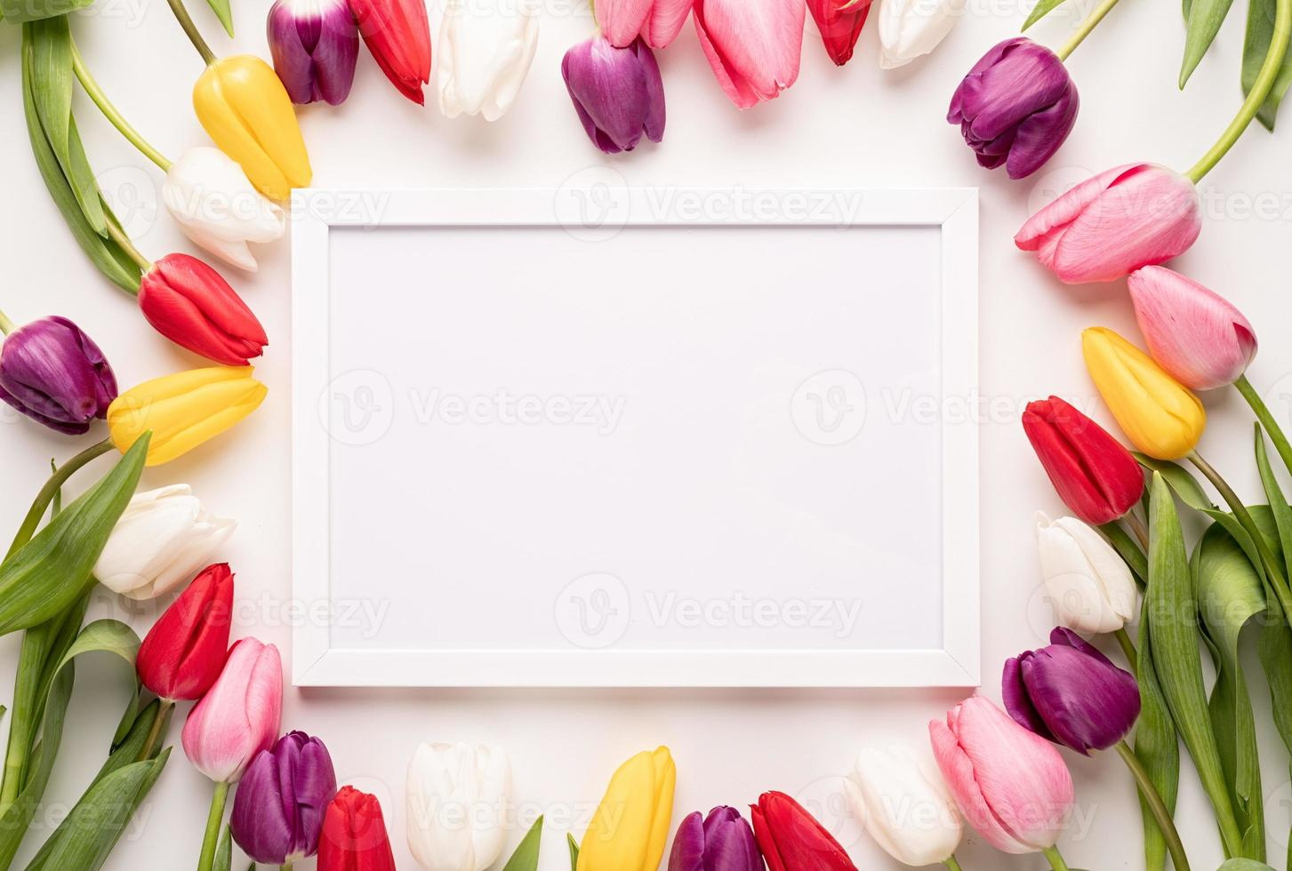 White frame with colorful spring tulips top view over white background photo