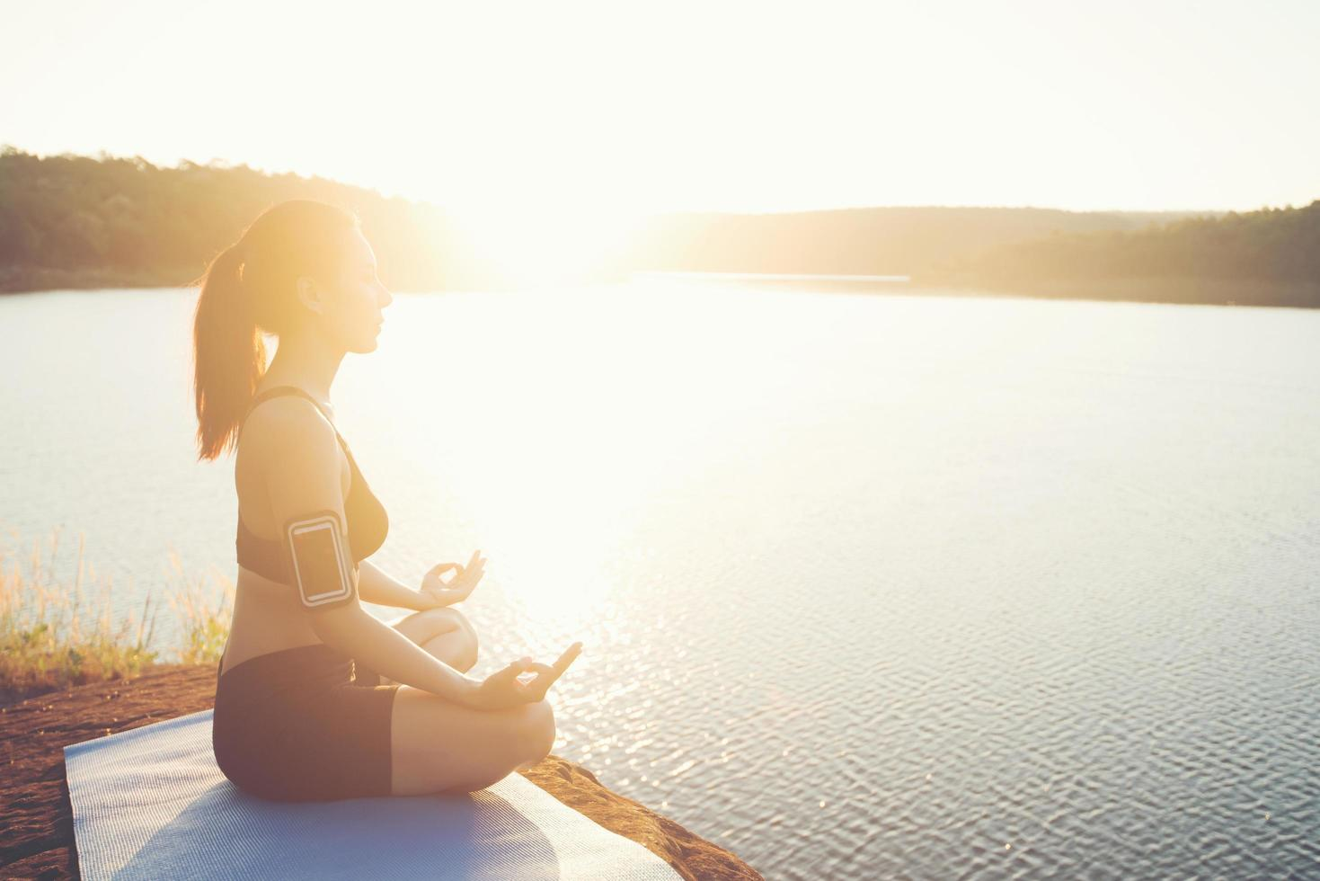 Young healthy woman is practicing yoga at mountain lake during sunset. photo
