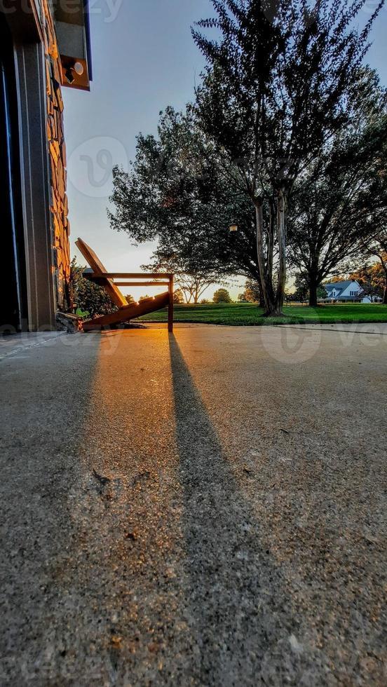 beautiful sunset with shadows of adirondack chair near house photo