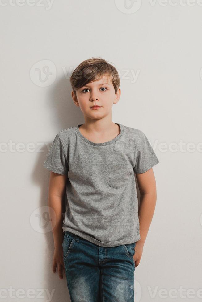 un niño con cara de miedo junto a la pared blanca, camisa gris, jeans foto