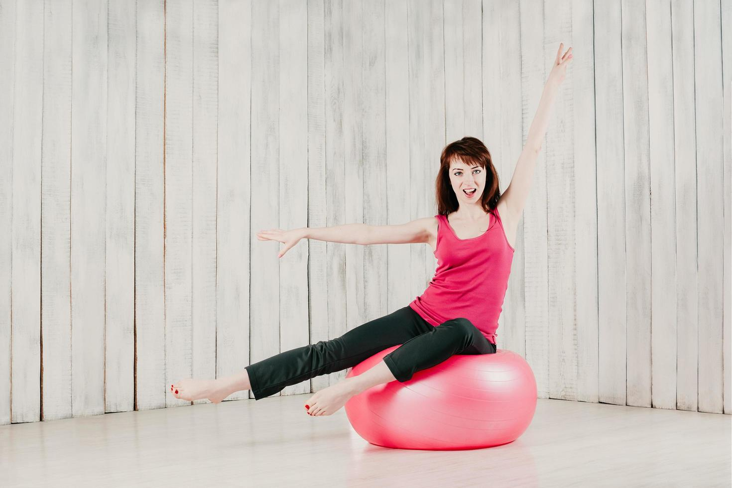 A girl in a pink top, sitting on a pink fitball in a gym photo