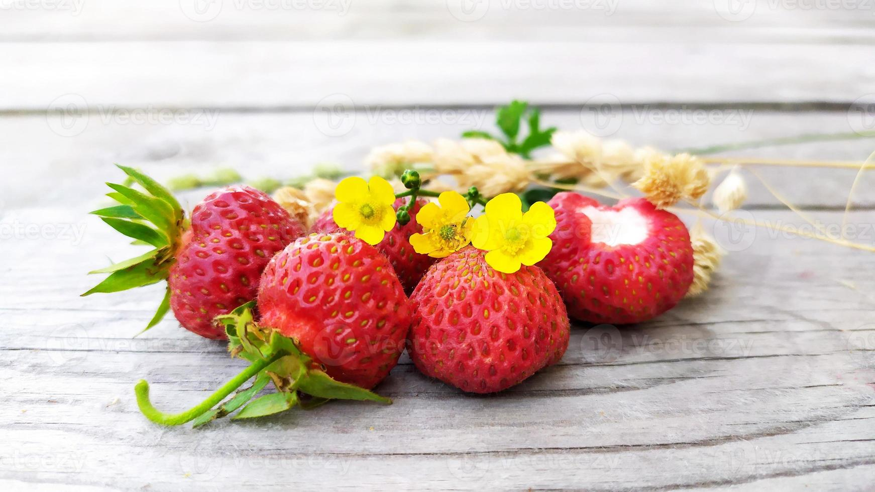 Strawberry close-up with dry yellow sprigs of sedge photo
