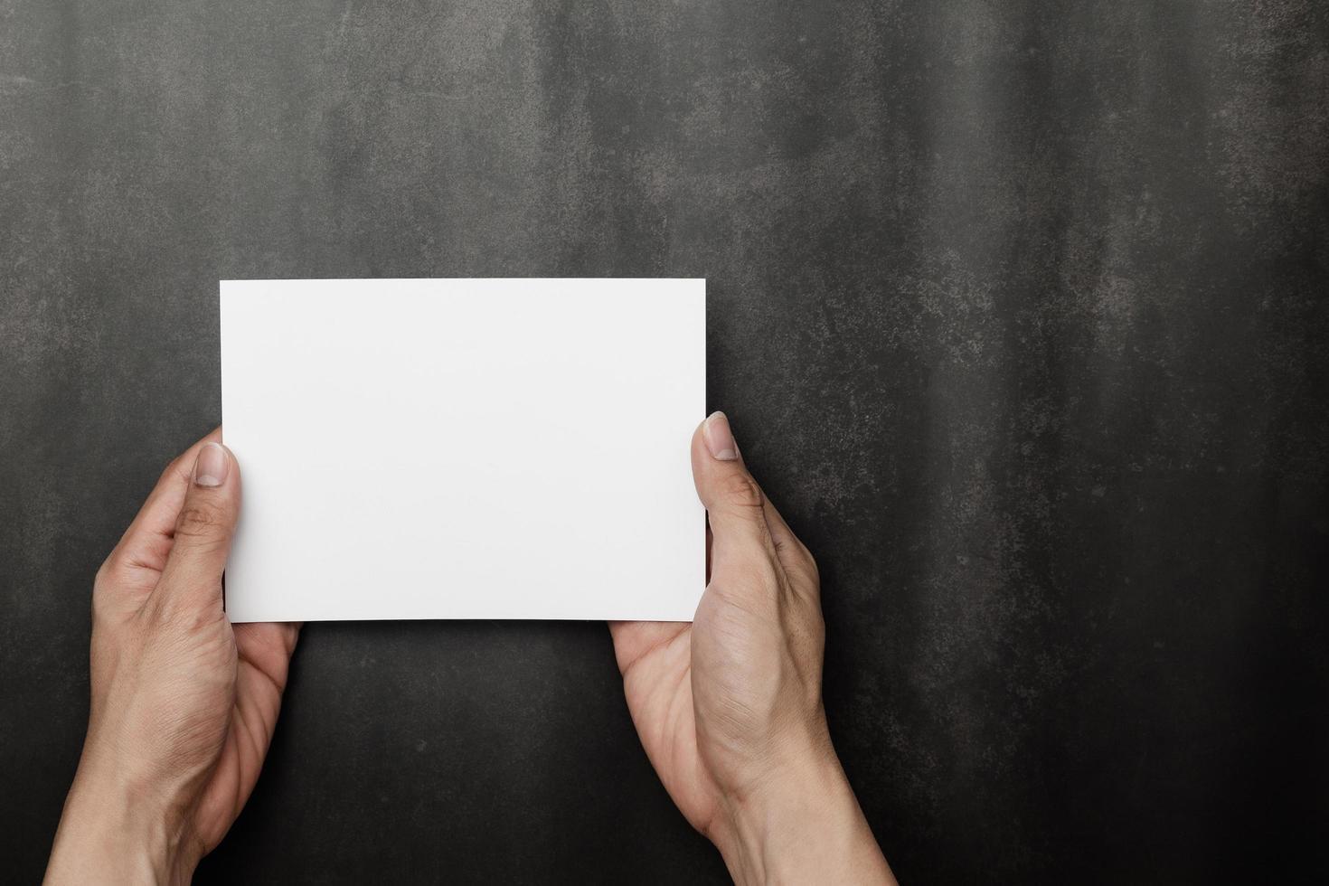 mano que sostiene la maqueta de la tarjeta de invitación, plantilla de tarjeta de felicitación en blanco. foto