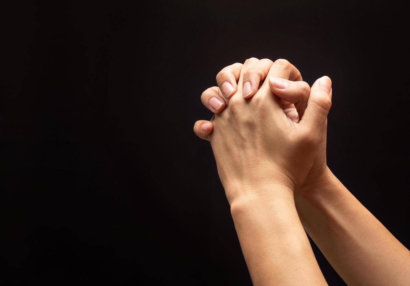 Hands out in prayer on black background photo