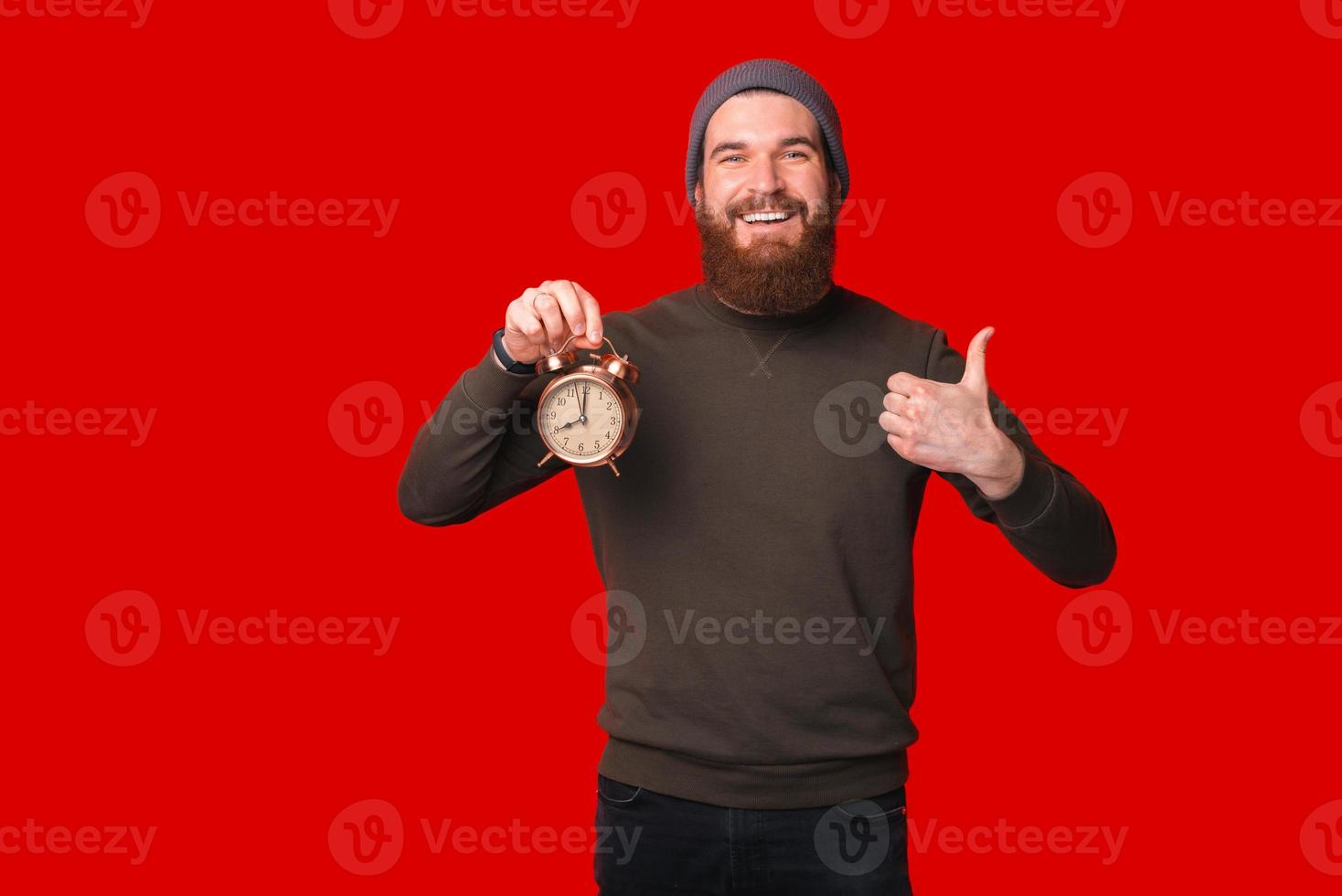 Photo of man with beard holding alarm clock and showing thumb up