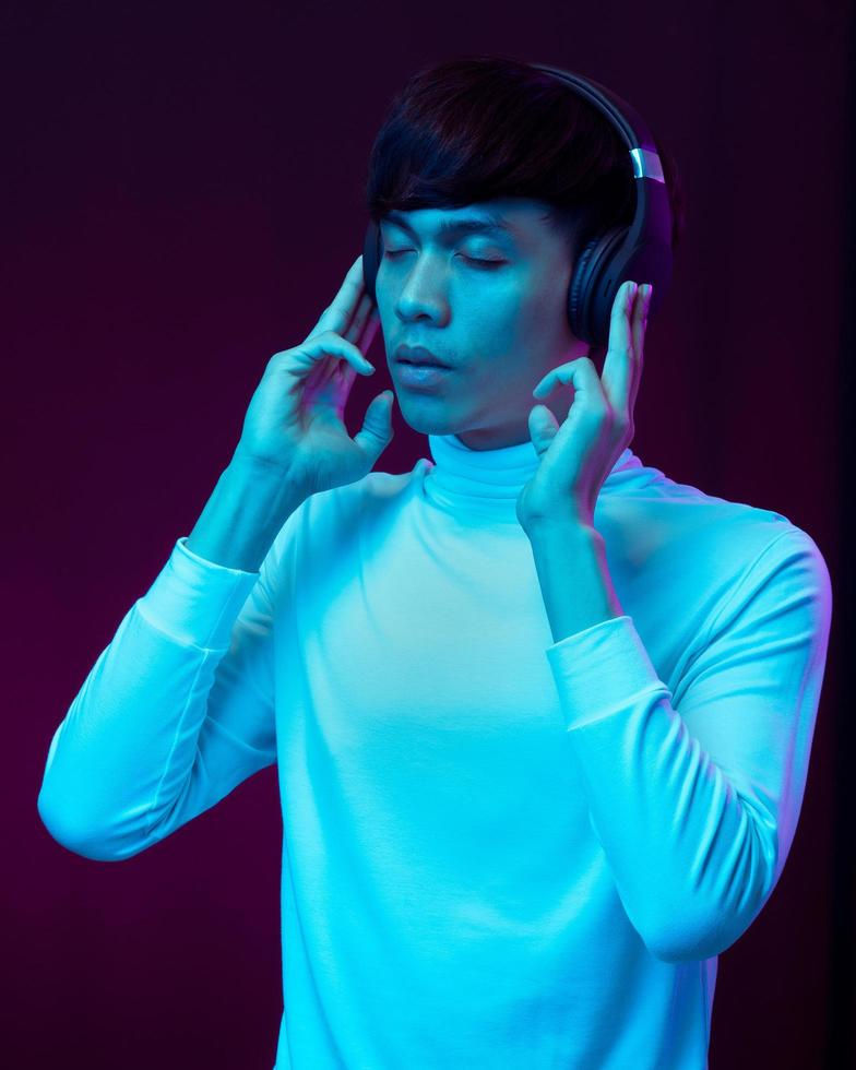 Young asian man listening music with headphone in neon light photo