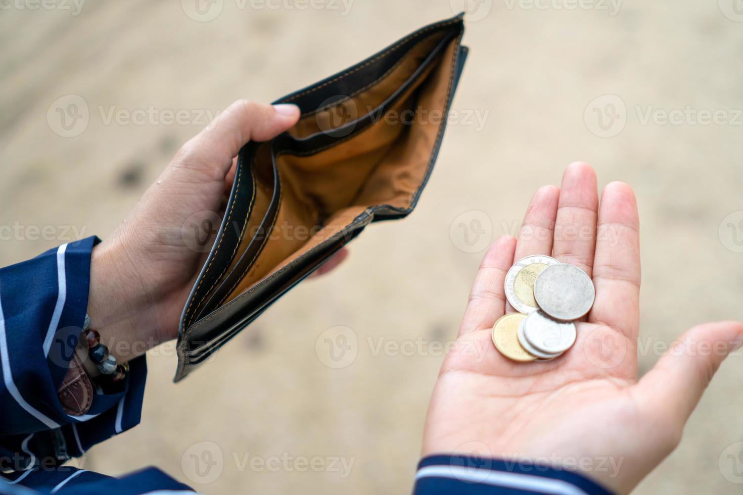 mujer sostiene un bolso vacío y monedas en la mano. foto