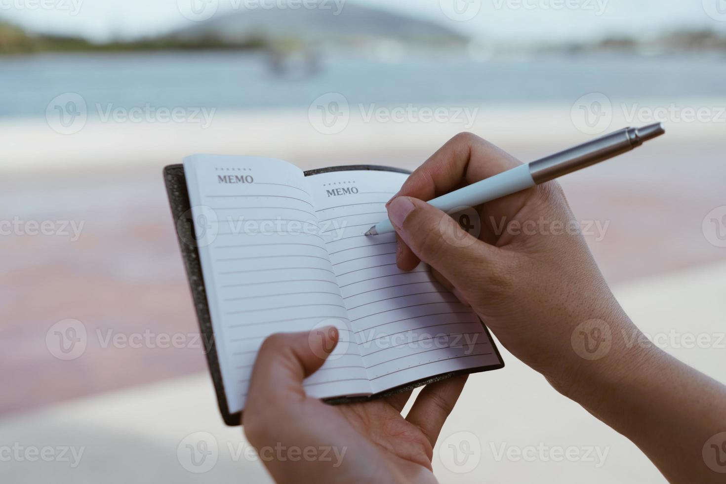 Woman hand writing down in small white memo notebook for take a note. photo