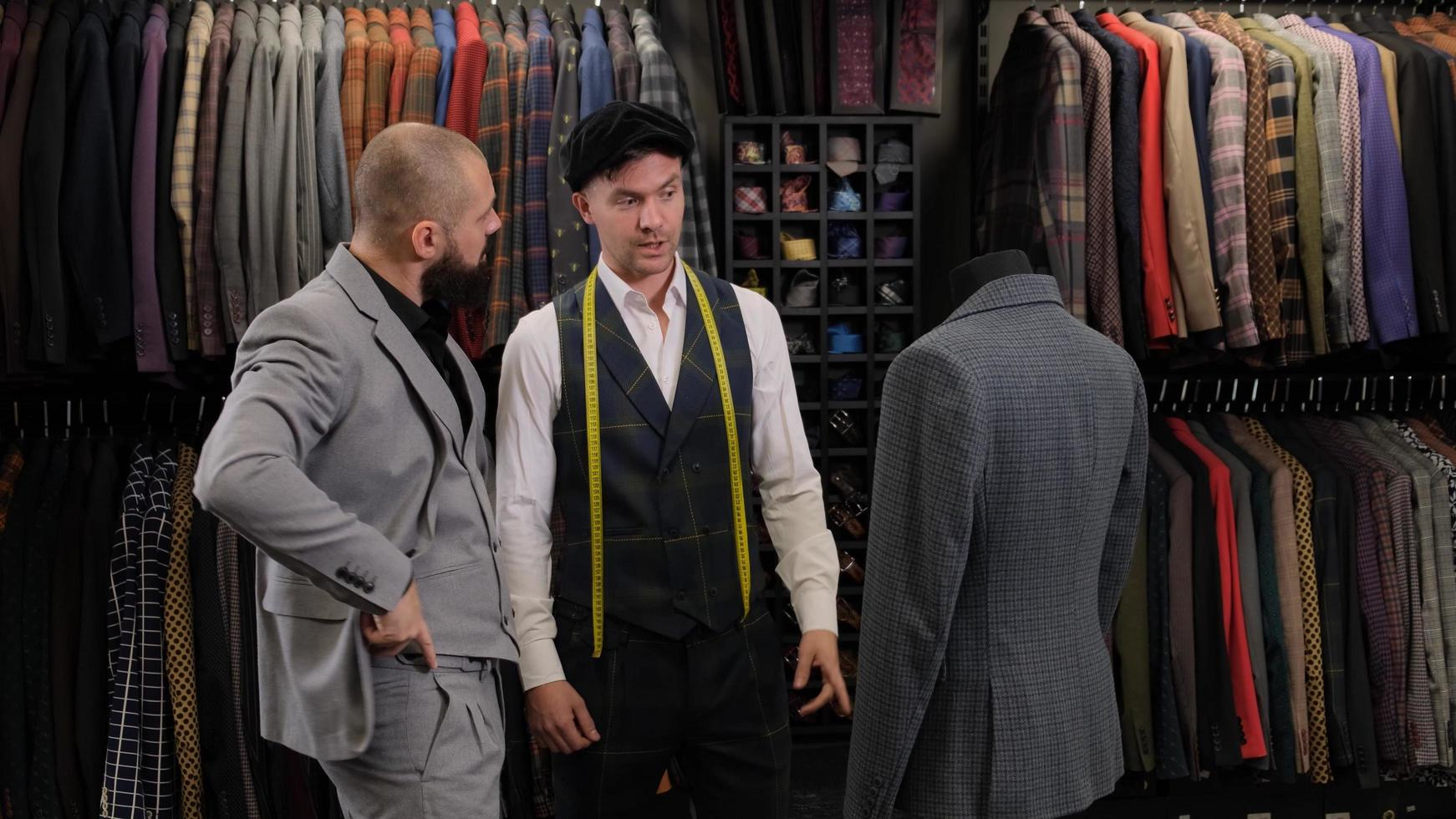 Slow motion of handsome man choosing a suit design with tailor in atelier. designer presenting the costume on the menequin to the buyer photo
