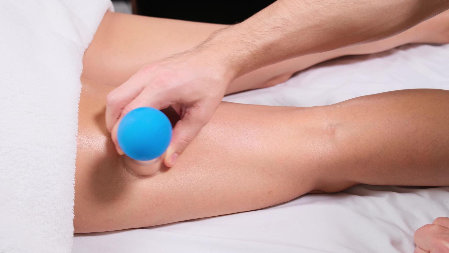 young woman receiving vacuum leg massage. masseur sets vacuum cup on leg. close up photo
