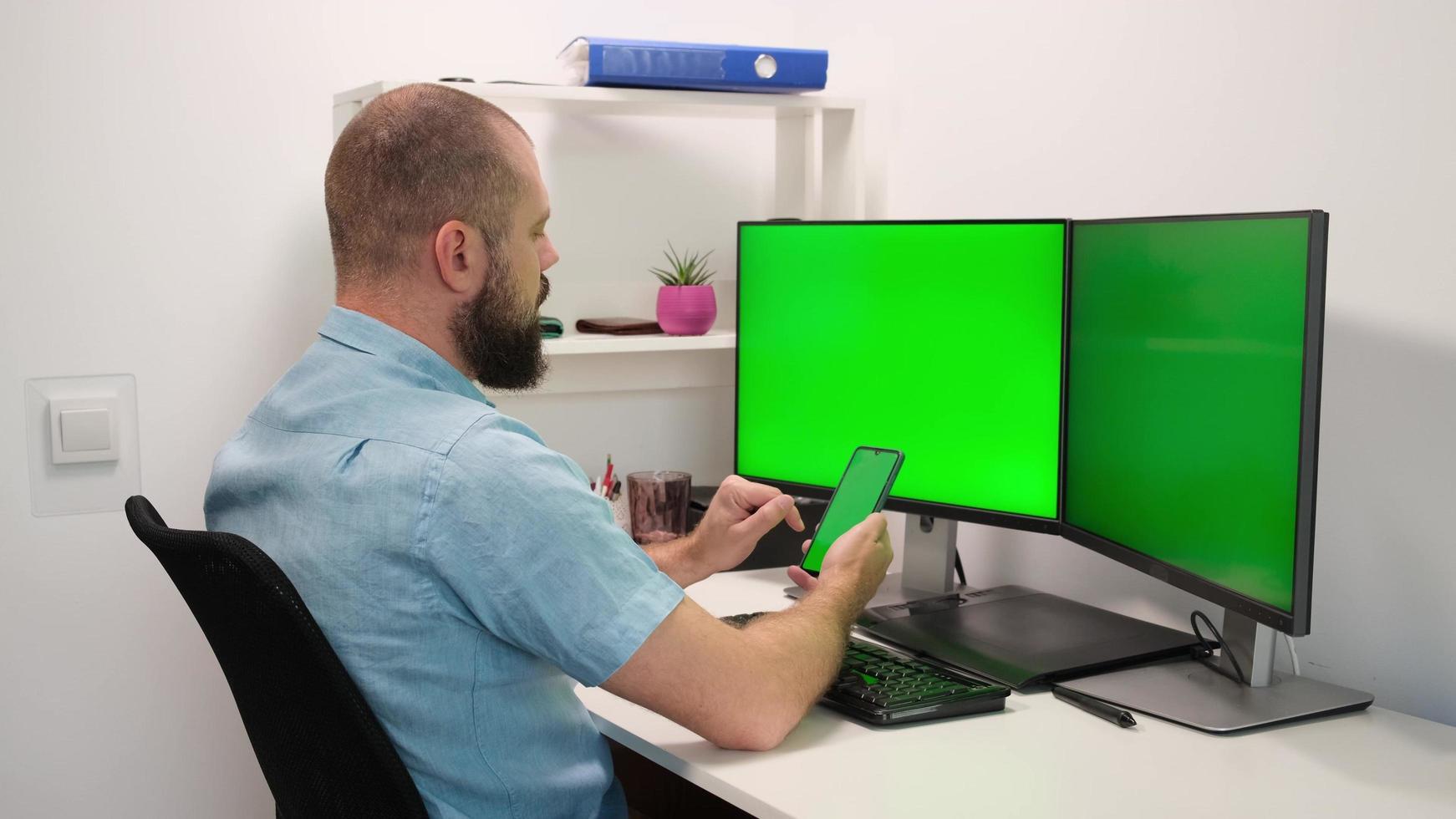 Hombre de negocios trabajando y escribiendo en un teléfono móvil y una computadora con dos monitores, trabajo multitarea, pantalla verde foto