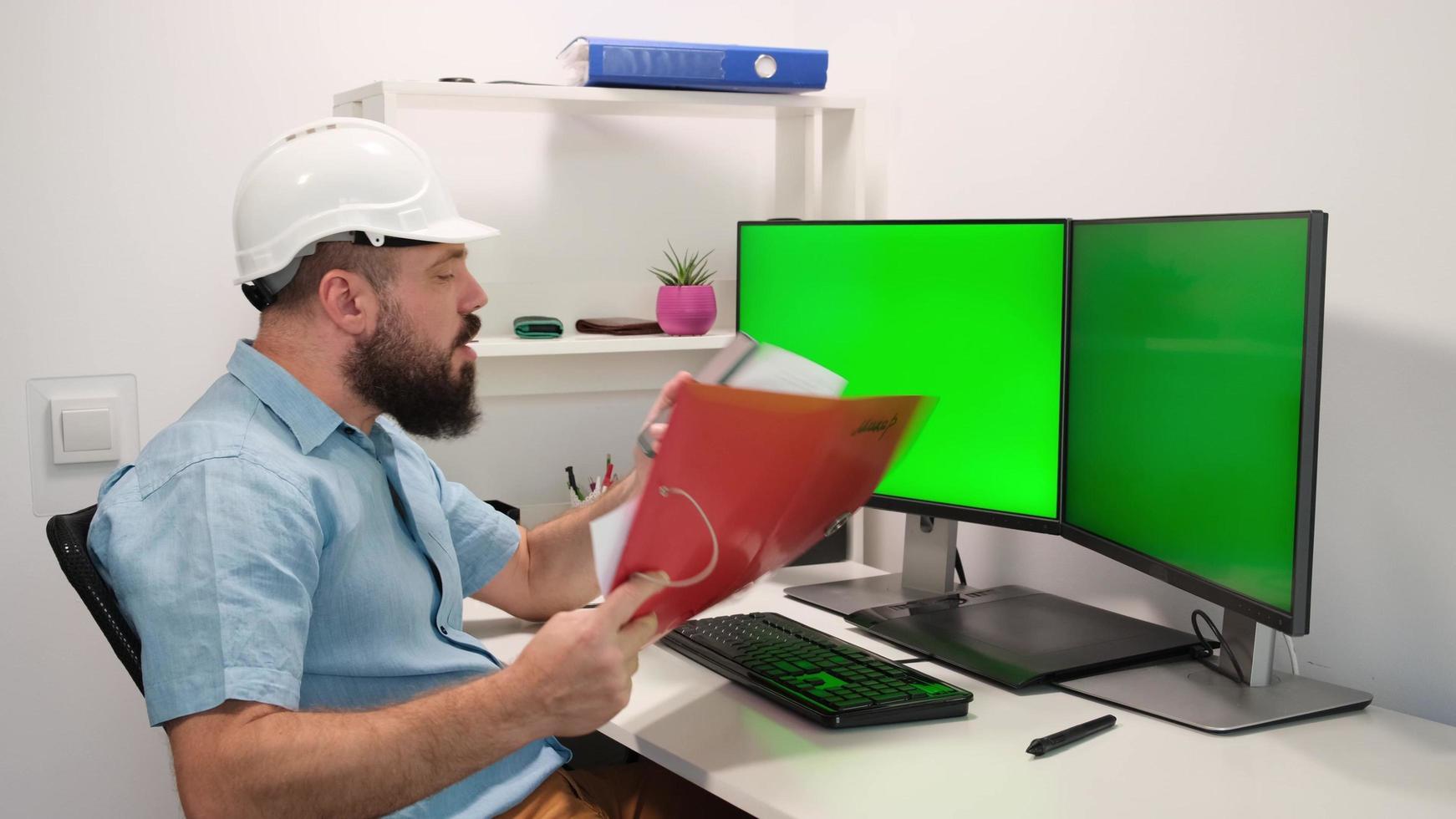 hombre en casco trabajando en casa detrás de la computadora con dos pantallas verdes para rastrear y pegar su información. acogedor interior de la casa, alto concepto tecnológico. foto