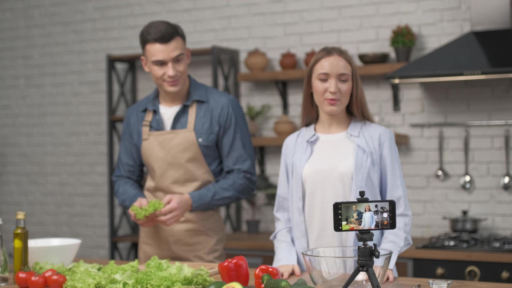 Pareja joven cocinando juntos y grabando video blog de comida en la cámara en la cocina de casa foto