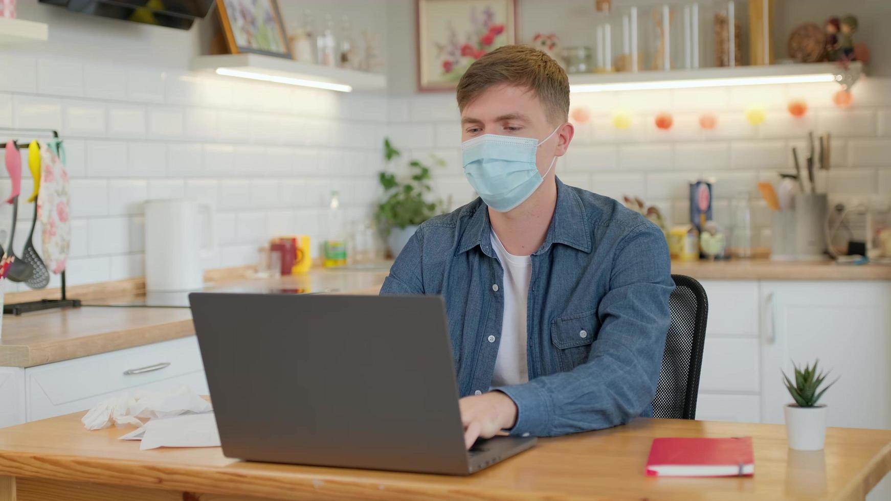 Hombre caucásico con una máscara medicinal en la cara está trabajando desde casa en la computadora portátil foto