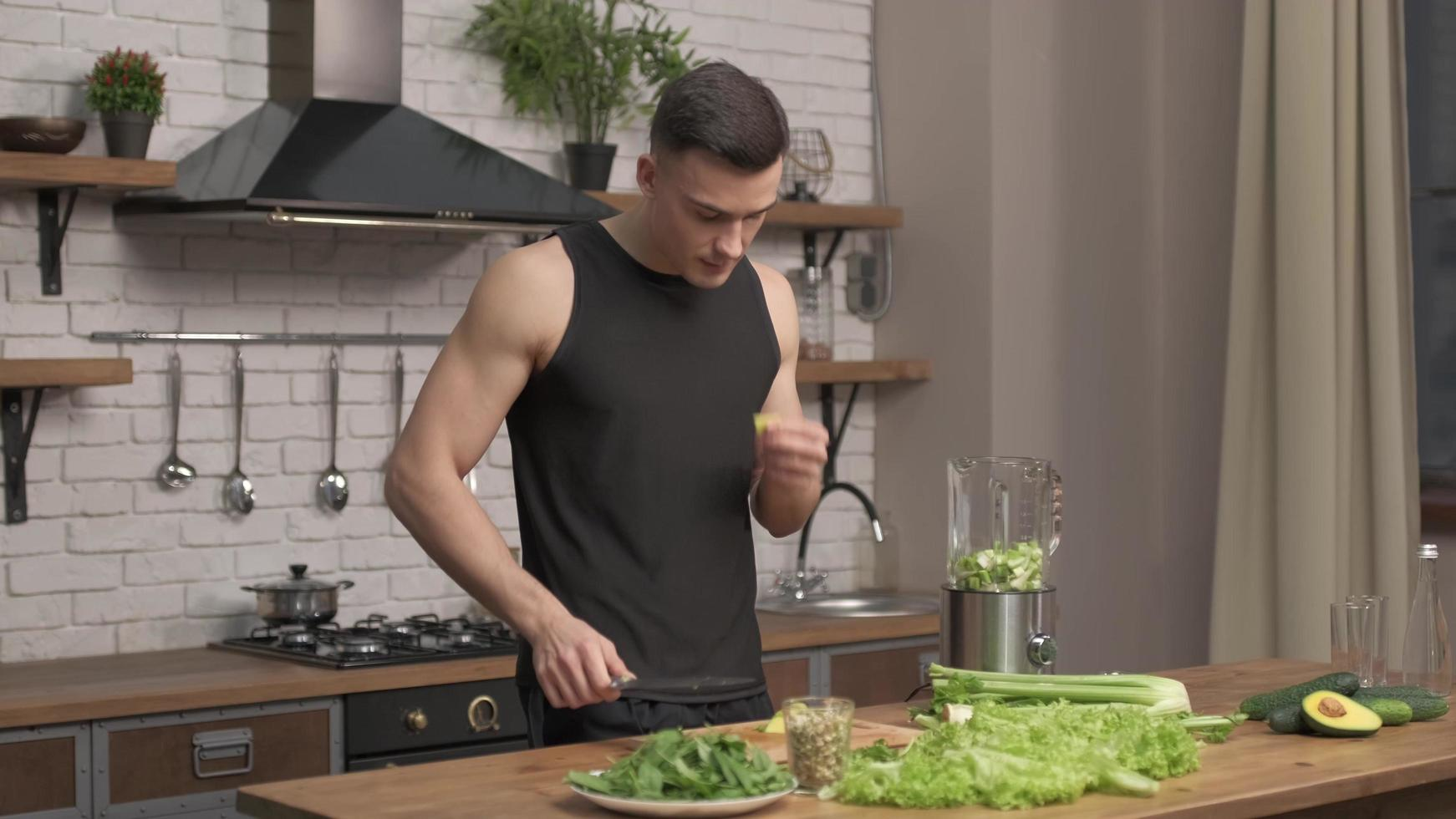 athlete man preparing ingredients for smoothie in a modern kitchen. Preparation of vegetables for detox in blender. avocado, celery, cucumber in liquidizer silver pot in background. Full HD photo