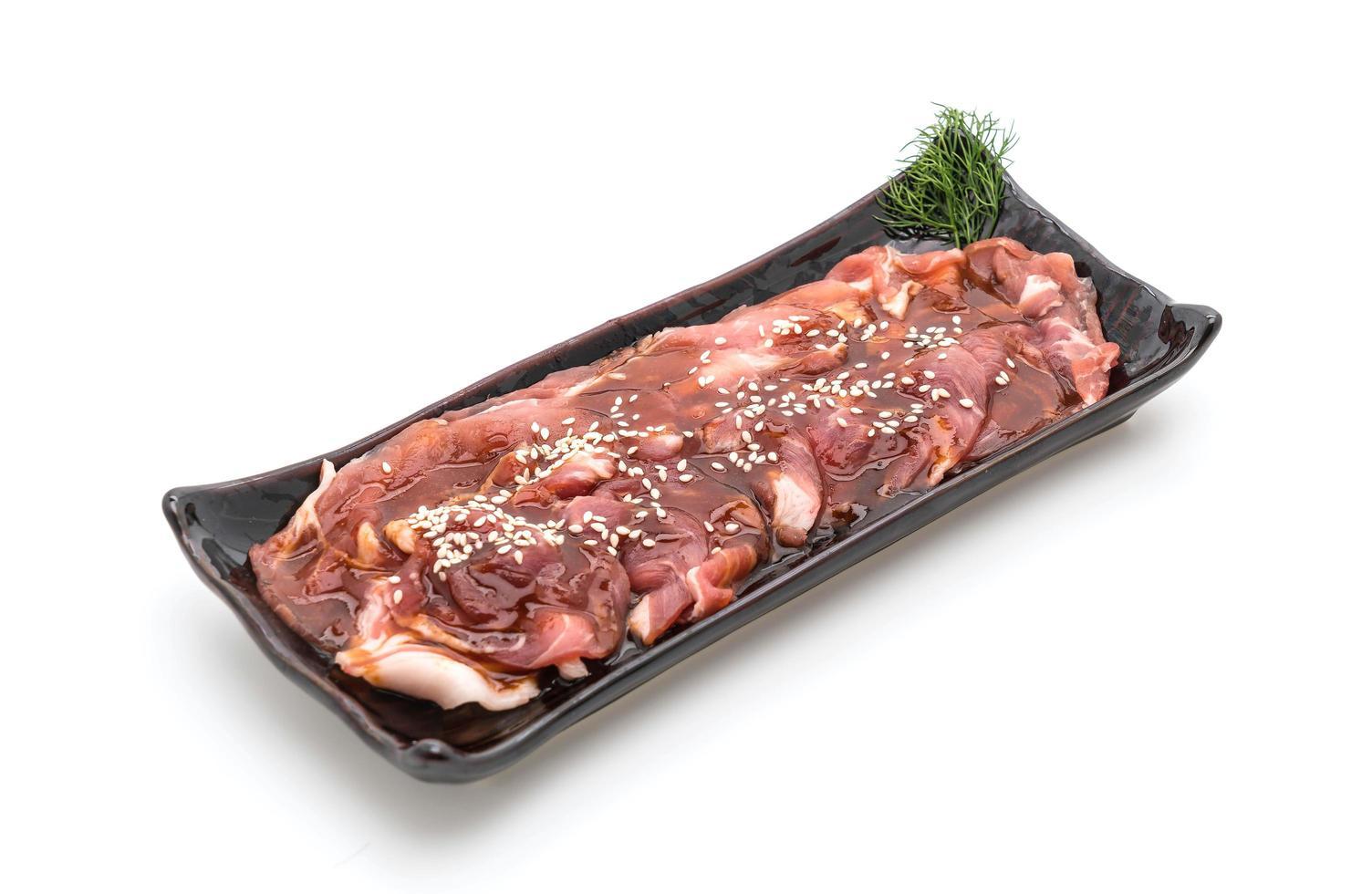 Carne de cerdo fresca en rodajas con salsa y sésamo sobre fondo blanco. foto