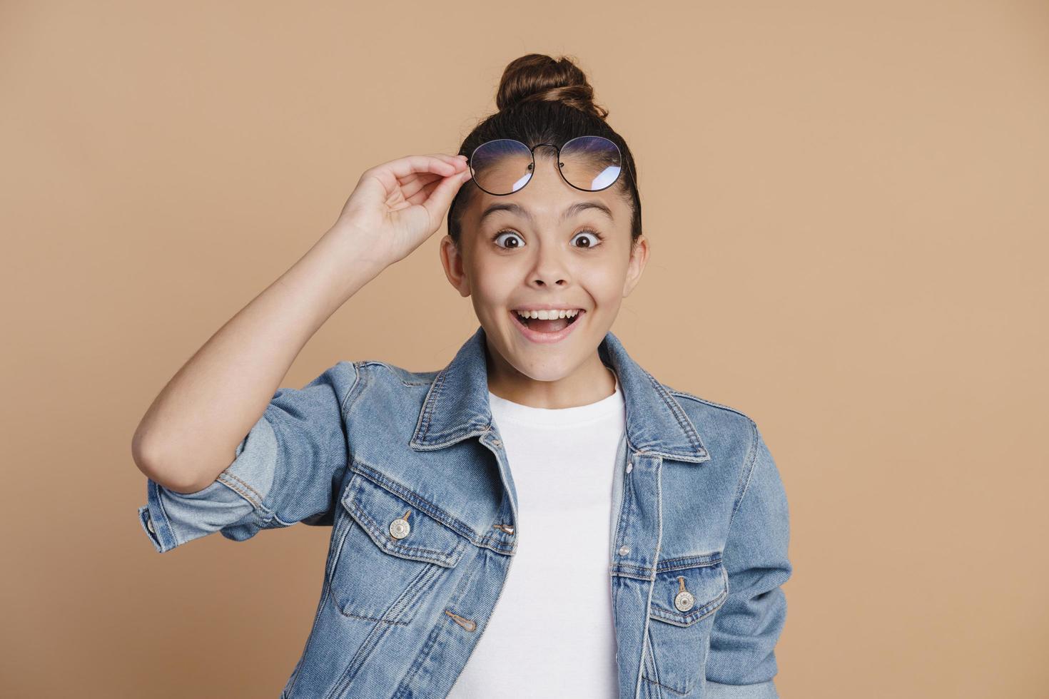 Amazed, cute teenage girl raised her glasses. Surprised little girl photo