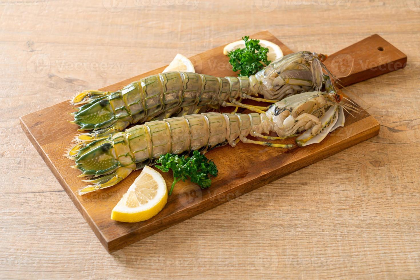 Fresh mantis shrimp with lemon on wood board photo