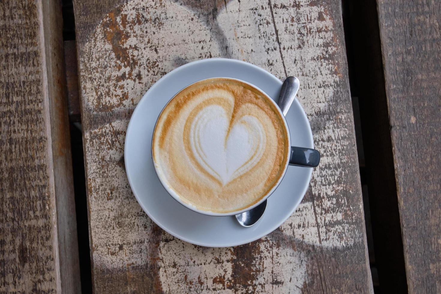 Top view of a cup of cappuccino with heart foam on a wooden surface photo