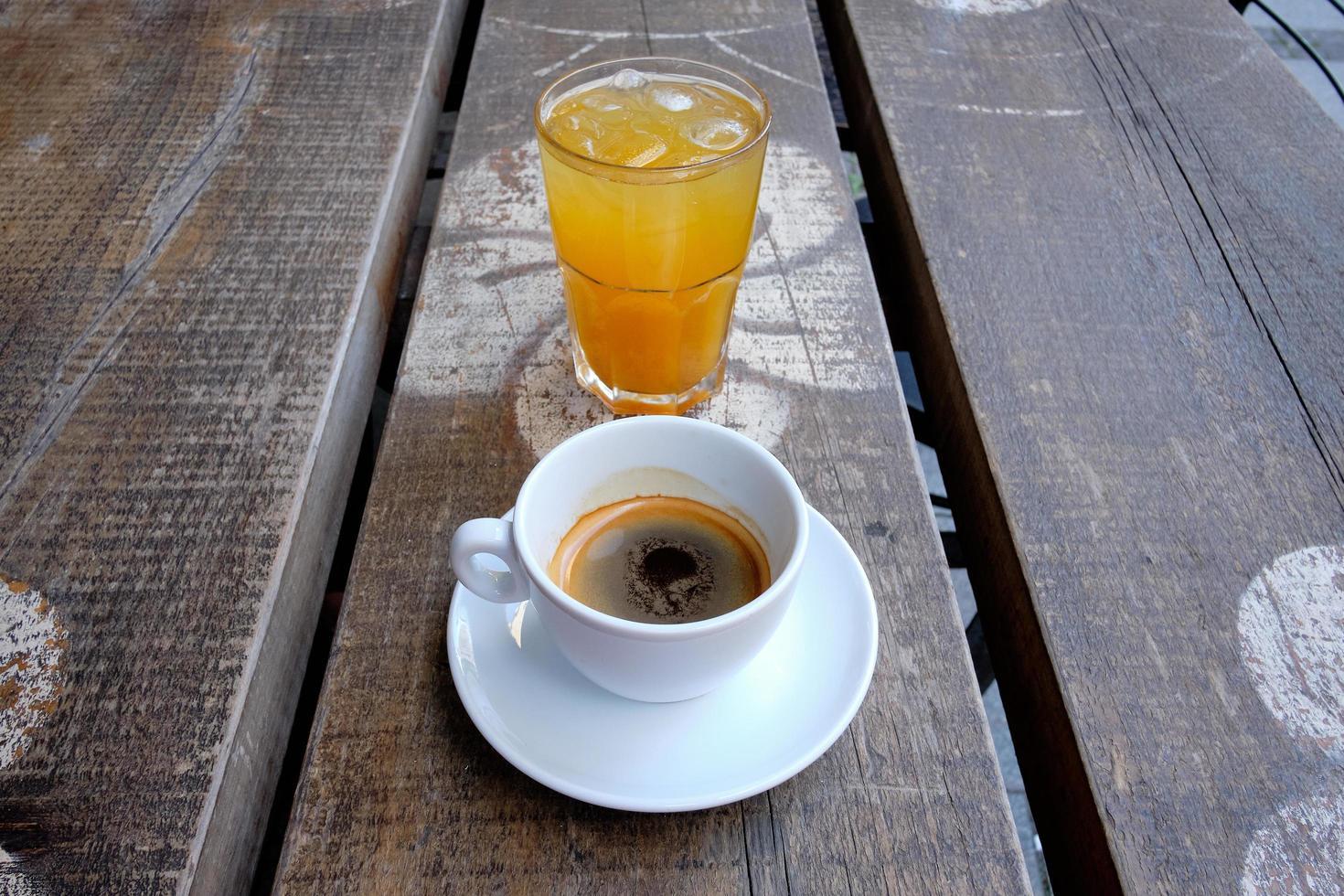 taza de café y un vaso de jugo de naranja fresco en una tabla de madera foto