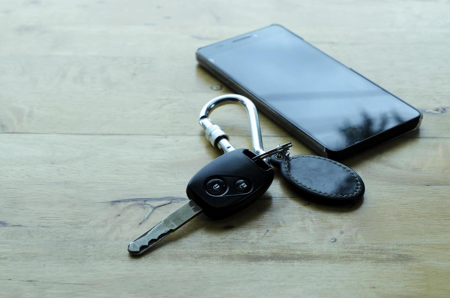 Car key and smartphone on wooden table backgrounds photo