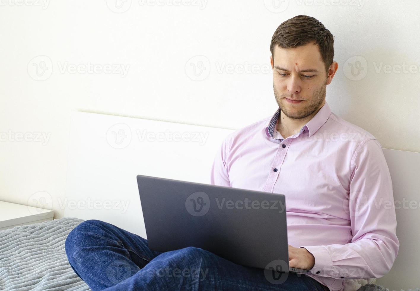 A man in a shirt and jeans solves work issues remotely. photo