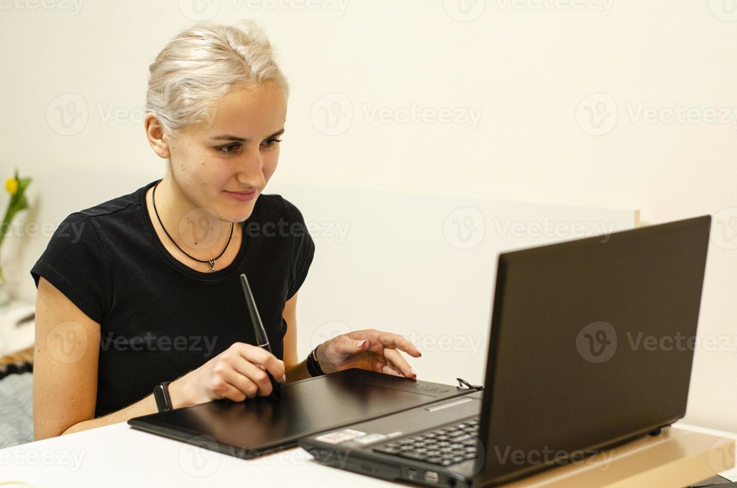 la niña aprende a dibujar en una tableta gráfica. computadora portátil. foto