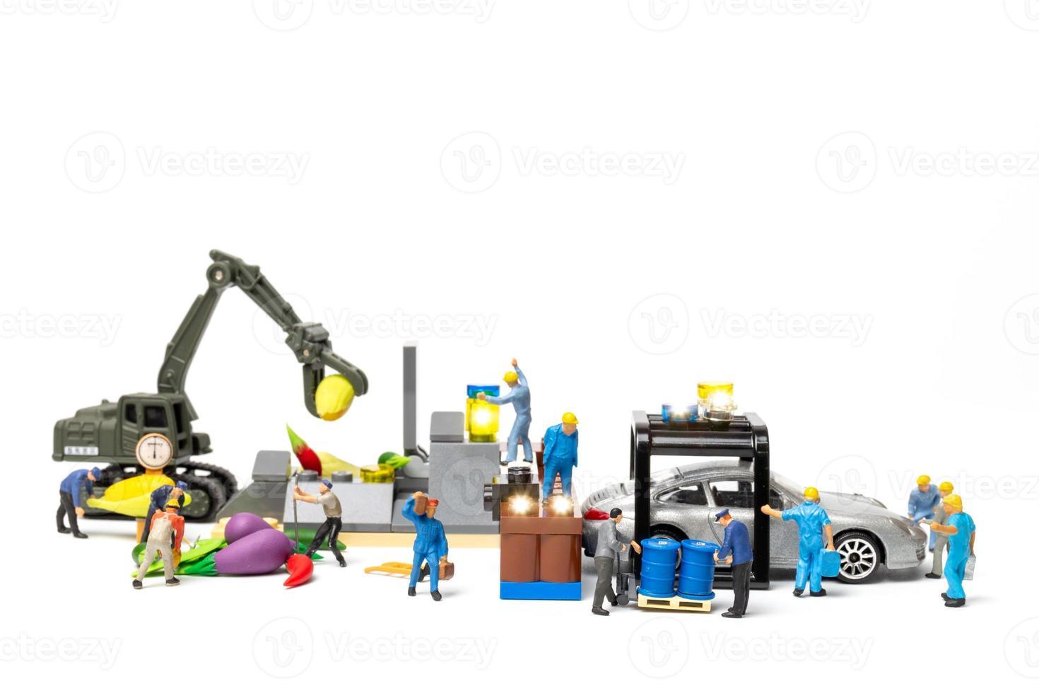 La gente en miniatura trabaja en la estación de bombeo de biocombustible foto