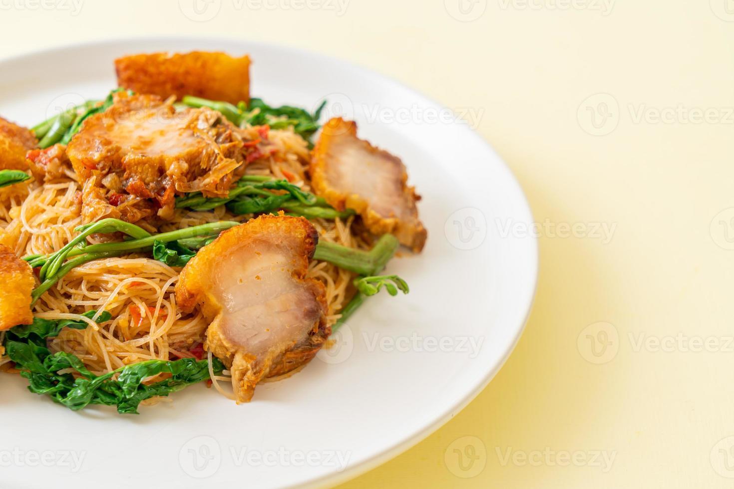 Fideos de arroz salteados y mimosa de agua con panceta de cerdo crujiente foto