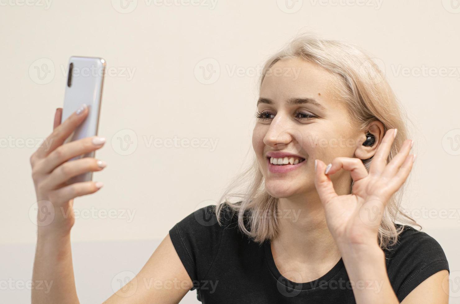 chica se comunica por videollamada. audífonos inalámbricos. foto