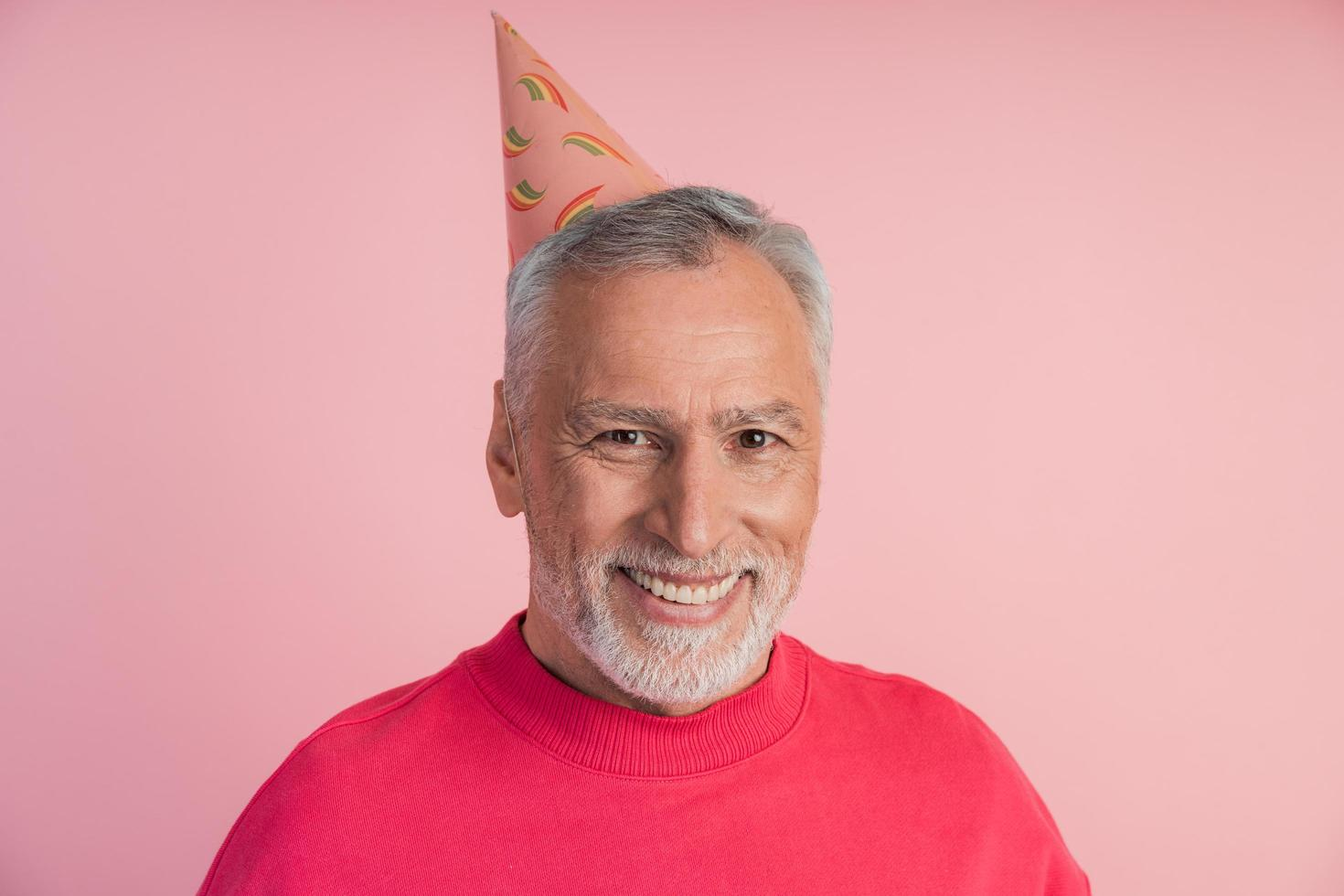 Cheerful, smiling man in a festive hat on a pink background. photo