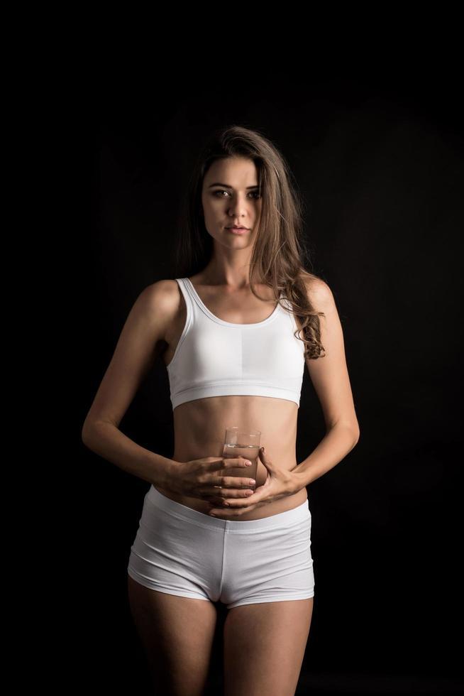 modelo de fitness femenino sosteniendo un vaso de agua foto