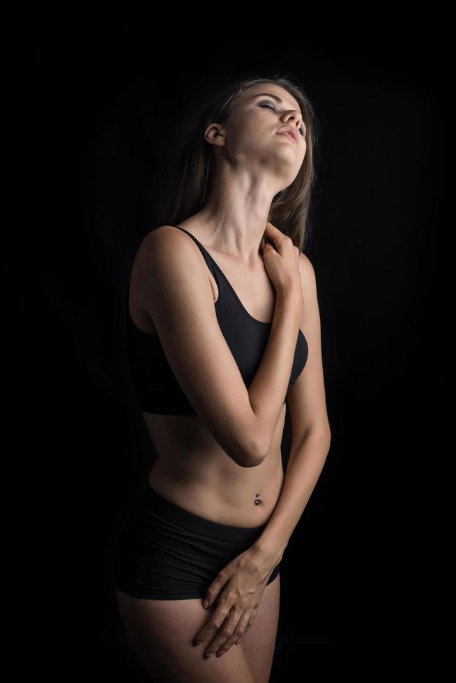 Beautiful woman with healthy body on black background photo