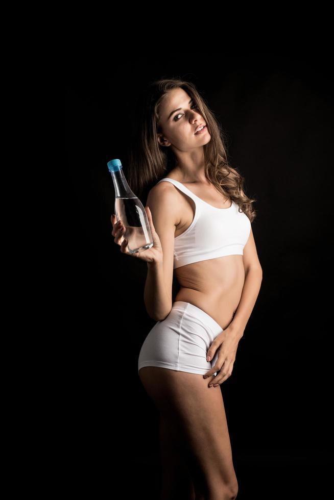 Female fitness model holding a water bottle photo