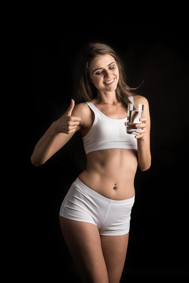 Female fitness model holding a water glass photo