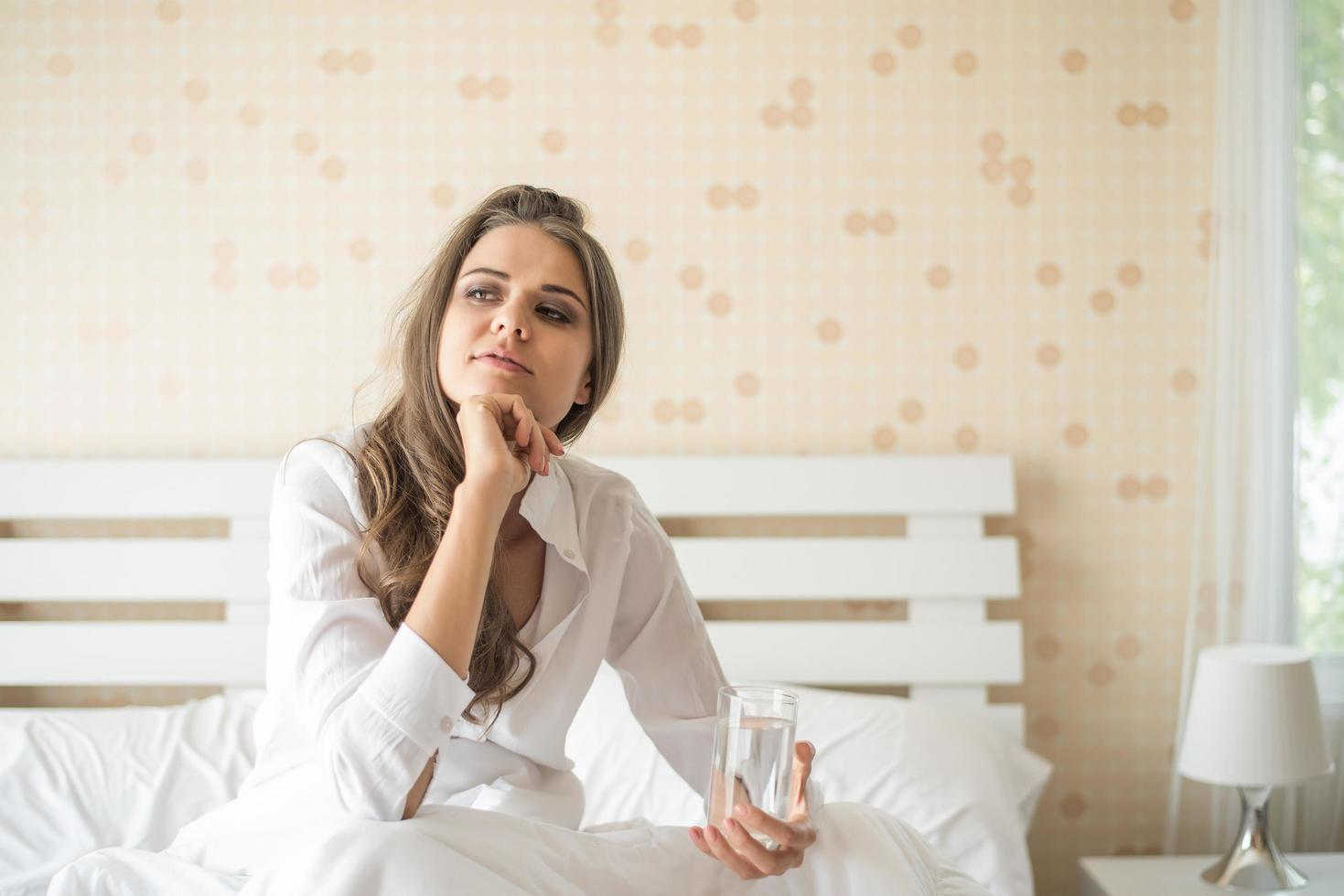 Beautiful woman drinking fresh water in the bed at the morning photo