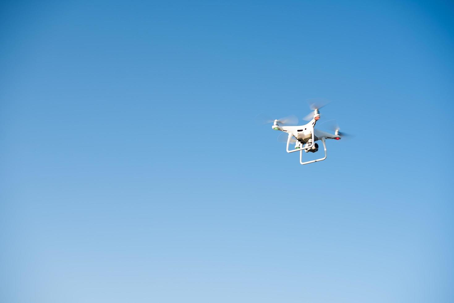 White drone fly in the sky recording a video photo