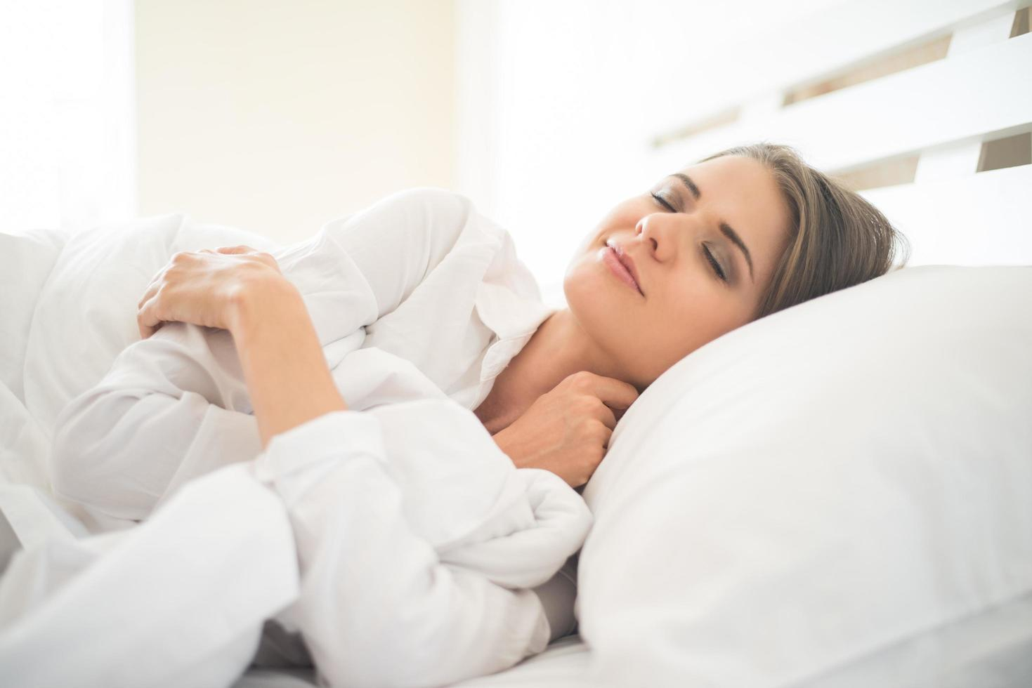 hermosa joven durmiendo en la cama foto