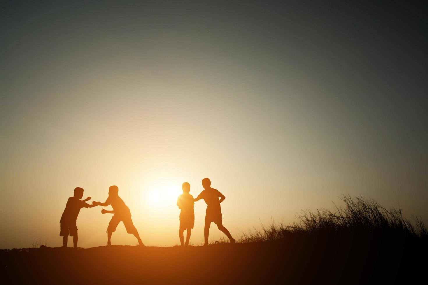niños jugando en el atardecer de verano tiempo feliz foto