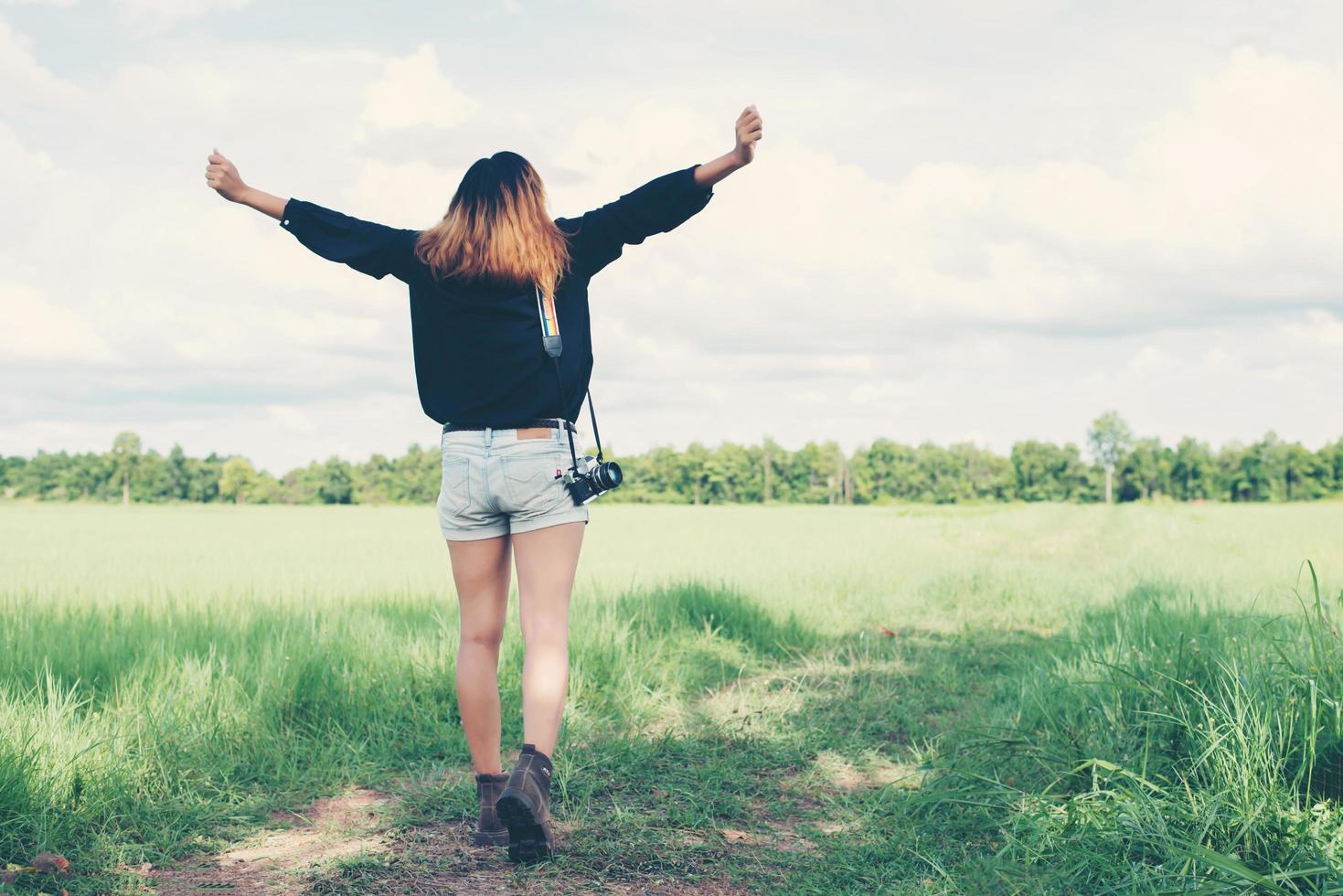 disfrutar de la parte posterior de la mujer joven que lleva la cámara retro en el campo de hierba. foto