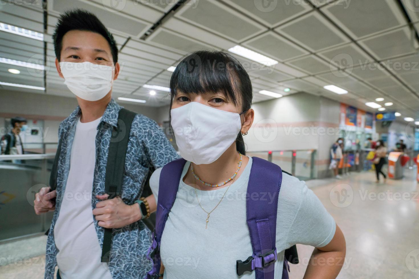 Pareja asiática con máscara de salud para viajar en metro en Tailandia foto