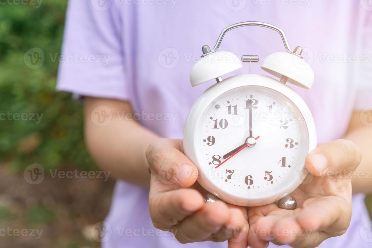 Selective focus of alarm clock with nature bokeh background photo