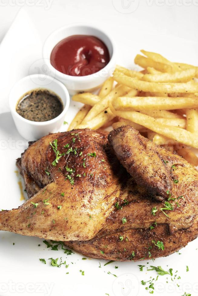 Roast rotisserie half chicken with french fries simple meal on white plate photo
