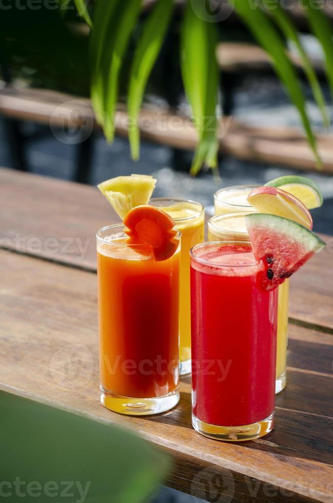 Selección de vasos de jugo de fruta orgánica fresca mixta en la soleada mesa de jardín foto