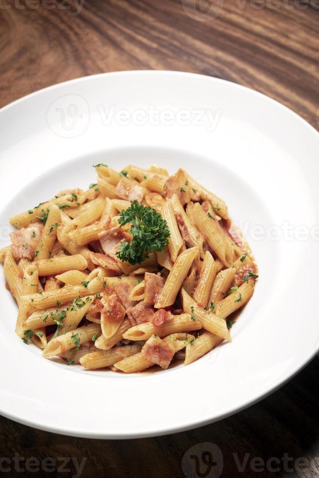 Penne amatriciana pasta con salsa de tomate y jamón sobre fondo de tabla de madera foto