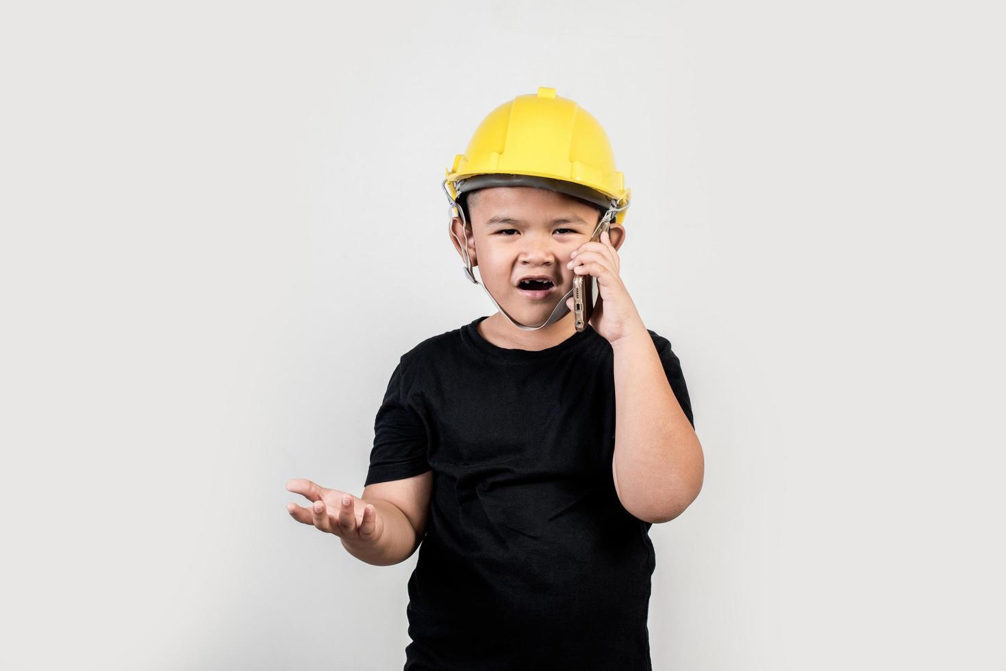 niño ingeniero hablando de teléfono inteligente sobre el proyecto con el socio. foto