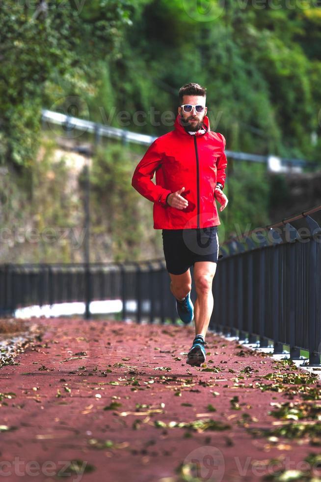un atleta corre en el carril bici en el otoño foto